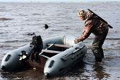 stock photo of hunter  - the hunter with motor rubber boat on  the river - JPG