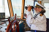 pic of observed  - Old experienced captain observes using binoculars by left hand and holding radio comunication equipment by right hand - JPG