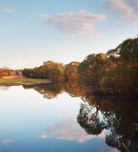 image of reflection  - Trees on banks of river reflected in  water - JPG