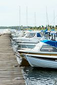 pic of marina  - Several boats moored in the marina attached to wooden bridge - JPG