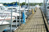 picture of marina  - Several boats moored in the marina attached to wooden bridge - JPG