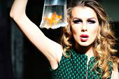 picture of little girls photo-models  - Dramatic young girl with bright makeup and blonde curly hair holding cellophane package aquarium with goldfish horizontal photo