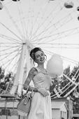 pic of candy cotton  - Girl with a tattoo with cotton candy in the hands of an amusement park on the background of traits kolesa - JPG