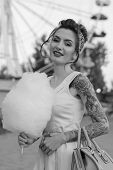 image of candy cotton  - Girl with a tattoo with cotton candy in the hands of an amusement park on the background of traits kolesa - JPG
