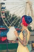 picture of candy cotton  - Girl with a tattoo with cotton candy in the hands of an amusement park on the background of traits kolesa - JPG