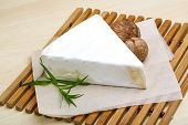 image of brie cheese  - Brie cheese with wallnut and terragon on wood background - JPG