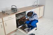 picture of dishwasher  - Young African Repairman Repairing Dishwasher In Kitchen - JPG