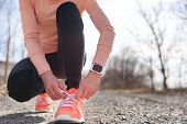 Постер, плакат: Running shoes and runner sports smartwatch Female runner tying shoe laces on running trail using sm