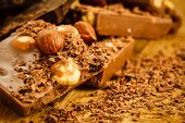 pic of hazelnut  - Closeup milk chocolate pieces hazelnuts and shavings curls on wooden table - JPG