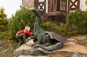 stock photo of alligator baby  - Little boy plays near a statue of a dragon - JPG