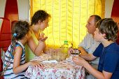stock photo of railroad car  - family of four talking  at a table in the dining car of the train - JPG