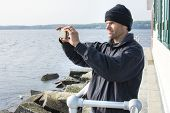 stock photo of beanie hat  - Caucasian man dressed in black jacket and beanie takes cell phone photo of scenic view of bay at the lighthouse at end of breakwater in Rockland Maine - JPG