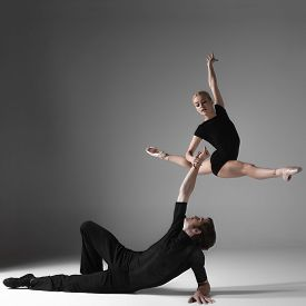 stock photo of  dancer  - The two young modern ballet dancers in black suits over gray studio background - JPG