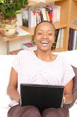 Happy African American young woman using a laptop at home