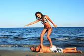 foto of grils  - Closeup of happy couple at the beach gril surfing on her boyfriend - JPG