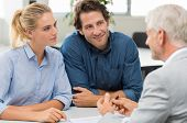Businessman explaining loan policy to young couple. Happy couple discussing with a financial agent t poster
