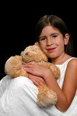 Young girl hugging Teddy bear isolated over a black background
