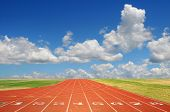 stock photo of race track  - Running track with eight lanes with sky and clouds - JPG