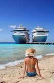image of cruise ship caribbean  - Woman relaxing on beach with cruise ships in background - JPG