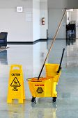 Mop bucket and caution sign on a web floor
