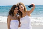 two beautiful friends on beach taking selfportrait with a cellphone camera