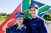 two south africa police officer saluting in front of south african flag
