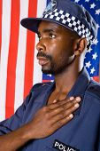 african american policeman pledging allegiance, background is USA flag