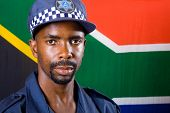 south africa police officer, background is south african flag