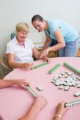 daughter teaching senior mother how to play mahjong game