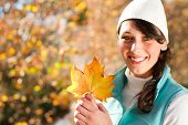 happy young woman in autumn forest holding golden tree leaves