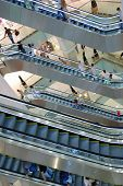 People in escalators at the mall. No brand names or recognizable faces. poster