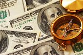 Antique compass over 100 dollar bills background