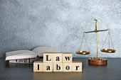 Wooden cubes with phrase LAW LABOR and scales on a table poster
