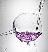 wine glass with pink liquid splashing