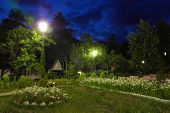 Evening Garden, Lanterns, Flower Beds, Trees Against The Background Of The Evening Sky poster
