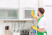 Young Man In Uniform Cleaning Microwave Oven In Kitchen poster
