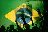 soccer fans supporting Brazil - double exposure of crowd in stadium with raised hands against Brazil poster