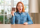 Redhead woman holding chocolate bar at home scared in shock with a surprise face, afraid and excited poster