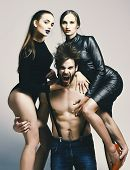 Women In Sexy Bodysuits Hug Bearded Macho. Guy With Naked Muscular Torso And Two Sexi Girlfriends. M poster
