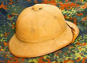 Retro helmet for tropical destination on a camouflage fabric.