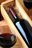 A red wine bottle in a wooden box filled with straw on a tasting room table with two glasses of pour