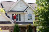 Man Cleaning The Upper Floor Exterior Of His Home Standing On The Lower Roof Using A Pressure Spraye poster
