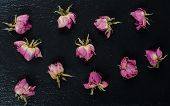 Buds Of Pink Faded Dry Roses Scattered On A Black Slate Background (flat Lay, Top View) poster