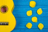 Body Of A Bright Yellow Ukulele Guitar And Petals Of Bright Yellow Handmade Roses Against A Bright B poster