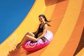 Young Pretty Woman On The Inflatable Ring Having Fun On The Orange Water Slide In The Aqua Park. Sum poster