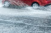 Splashes Of Water From Car Wheels. Car Traffic During Rainy Weather poster