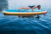 Pretty, Sporty Woman Planking On Paddleboard, Performing Plank Position On Sup Board At Sea poster
