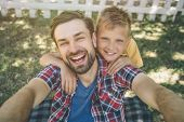 Selfie Of Happy And Bearded Guy And His Son. Man Is Holding Camera In Hands And Looking On It. He Is poster