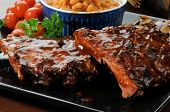 stock photo of baby back ribs  - A closeup photo of baby back ribs drenched in barbecue sauce with baked beans - JPG