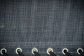 Black fabric background texture with rivets poster
